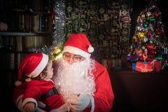 圣诞快乐和节日快乐!逗人喜爱的坐在发光的杉树附近的小孩女孩和圣诞老人项目 免版税库存照片