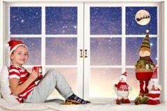 圣诞快乐和节日快乐!一个小孩子坐吃曲奇饼和饮用奶的窗口 免版税库存照片