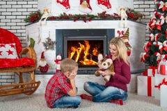 圣诞快乐和节日快乐! 使用与玩具狗的母亲和儿子由壁炉 免版税图库摄影