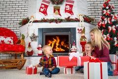 圣诞快乐和节日快乐! 坐由壁炉和开放圣诞节礼物的母亲和儿子从圣诞老人 免版税库存照片