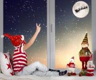 圣诞快乐和节日快乐!坐窗口和看在他的雪橇的小孩男孩圣诞老人飞行反对 库存图片