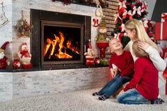 圣诞快乐和节日快乐! 妈妈和两个小儿子坐并且放松在圣诞树下由壁炉 图库摄影