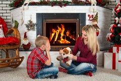 圣诞快乐和节日快乐! 妈妈给儿子一个玩具狗,孩子闭上了他的眼睛和惊奇的 免版税库存图片