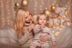 圣诞快乐和节日快乐!有坐在有礼物的装饰的屋子里的妈妈的小孩子女孩和光和享用 女儿 库存图片