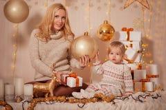 圣诞快乐和节日快乐!有坐在有礼物的装饰的屋子里的妈妈的小孩子女孩和光和享用 免版税库存图片