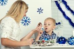 圣诞快乐和节日快乐! 母亲和儿子装饰与闪烁的杉木锥体 家庭创造圣诞节int的装饰 库存图片