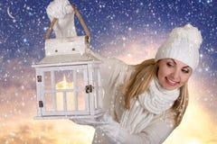 圣诞快乐和节日快乐! 白色被编织的衣裳的一个少妇拿着有一个蜡烛的一个灯笼 图库摄影