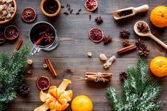 圣诞快乐在与温暖的饮料的冬天晚上 热的被仔细考虑的酒或酒用果子和香料在木背景 免版税库存图片