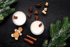 圣诞快乐在与酒精饮料的冬天晚上 蛋黄乳用姜饼曲奇饼、桂香和云杉在黑书桌上 免版税库存照片