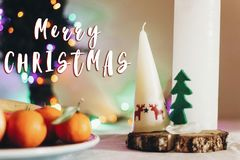 圣诞快乐在圣诞节土气桌上的文本标志与蜡烛 库存照片