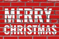 圣诞快乐在红砖墙壁上的问候文本 免版税库存照片