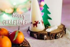 圣诞快乐在蜡烛的文本在r的标志与驯鹿和树 库存照片