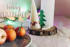 圣诞快乐在蜡烛的文本标志与驯鹿和圣诞节 免版税库存图片