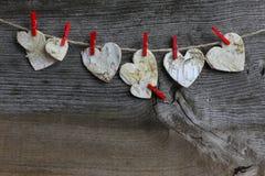 圣诞快乐垂悬的装饰桦树心脏和红色夹子 图库摄影