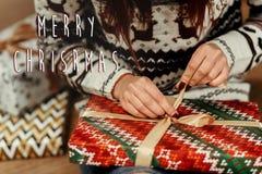 圣诞快乐文本与包裹圣诞节的妇女的标志问候 免版税库存照片