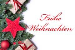圣诞快乐用在红色的德语在圣诞节背景borde 免版税库存图片