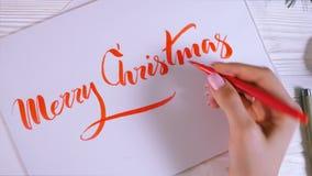 圣诞快乐祝贺 书法家写与红色墨水在白色卡片 书法 装饰品字体 艺术  股票视频
