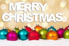 圣诞快乐许多五颜六色的与雪的球金黄背景 库存图片