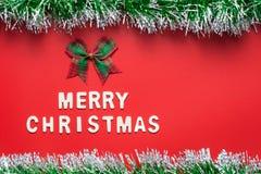 圣诞快乐词和丝带鞠躬与在红色背景的闪烁框架 免版税库存照片