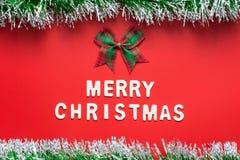 圣诞快乐词和丝带鞠躬与在红色背景的闪烁框架 库存照片