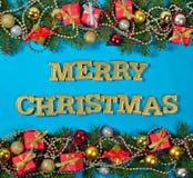 圣诞快乐金黄文本和云杉的分支和圣诞节deco 图库摄影