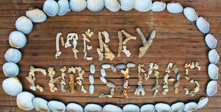 圣诞快乐题字手工制造与在木背景的海珊瑚 免版税库存照片