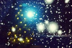 圣诞快乐!冷淡的冬天圣诞夜-在多雪的背景的不可思议的轻的彩色小灯在暴风雪期间的森林里和 免版税库存照片
