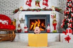 圣诞快乐! 一个小男孩在圣诞树和壁炉附近坐并且读与新年` s传说的一本书 免版税库存图片