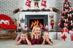 圣诞快乐! 一个年轻母亲和两个儿子在地毯说谎在树下 家庭休息在圣诞树下由 免版税库存图片