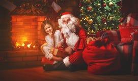 圣诞快乐!圣诞老人和儿童女孩在Chr的晚上 库存照片
