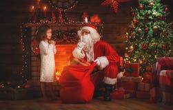 圣诞快乐!圣诞老人和儿童女孩在Chr的晚上 免版税图库摄影
