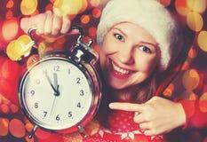 圣诞快乐!圣诞节帽子的妇女有闹钟的 免版税库存图片