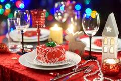 圣诞晚会或新年庆祝的美好的桌设置在家 有壁炉的舒适室和在ba的圣诞树 库存图片
