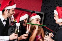 圣诞晚会朋友获得乐趣在棒 免版税库存照片