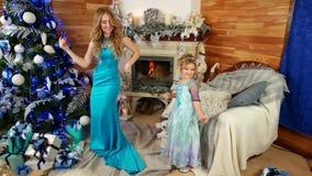 圣诞晚会,在圣诞树附近的家庭庆祝新年的,一个小逗人喜爱的女孩跳舞与母亲,冬天 影视素材