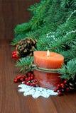 圣诞树、红色莓果和锥体,与一个灼烧的蜡烛 免版税图库摄影