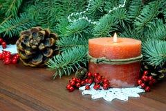 圣诞树、红色莓果和锥体,与一个灼烧的蜡烛 库存图片