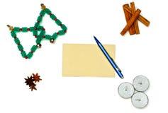 圣诞树、蜡烛和桂香与贺卡和笔 图库摄影