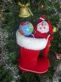 圣诞树与地球球的玩具圣诞老人项目,金钟,诗歌选,反对一绿色artificia的背景的Xmas红色起动 免版税库存照片