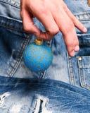 圣诞树中看不中用的物品在手中在牛仔布背景 冬天与闪烁装饰品的装饰球在男性手上 加法器 免版税库存图片