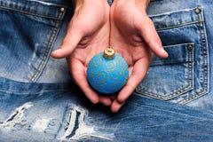圣诞树中看不中用的物品移交牛仔布背景 冬天与闪烁装饰品的装饰球在男性手上 加法器 库存照片