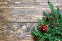 圣诞树分支与红色球和杉木锥体装饰在木板的 库存图片