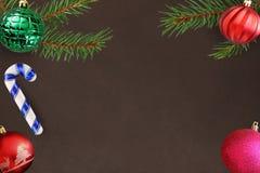 圣诞树分支用棍子、桃红色,红色波浪和绿色有肋骨球在黑暗的背景 免版税库存图片