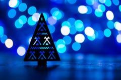 圣诞树剪影与装饰品的在蓝色bokeh backgro 免版税库存图片