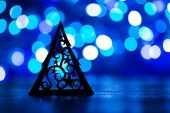 圣诞树剪影与装饰品的在蓝色bokeh backgro 免版税库存照片