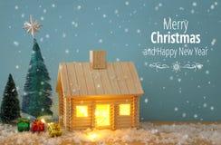 圣诞树和木房子的图象有光的通过窗口,在多雪的桌 库存照片