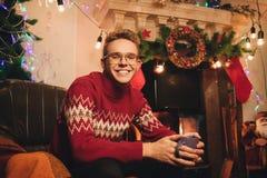 圣诞树和烟囱背景的微笑的人  免版税库存照片