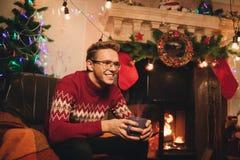 圣诞树和烟囱背景的微笑的人  免版税库存图片