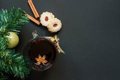 圣诞树和葡萄酒杯被仔细考虑的酒用曲奇饼和桔子在黑台式视图 图库摄影