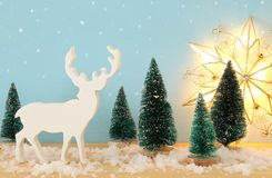 圣诞树和驯鹿的图象在多雪的木桌上 库存照片